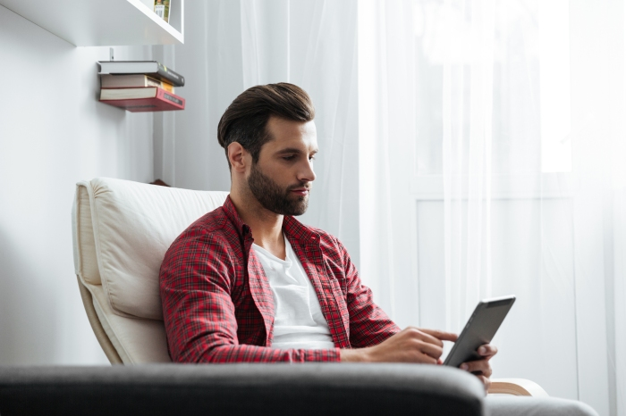 Handsome young bearded man using tablet computer